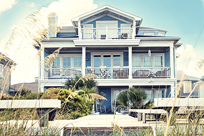 Ocean County home builder shows off back of blue, 3-story beach house with decks spanning both the 2nd and 3rd story